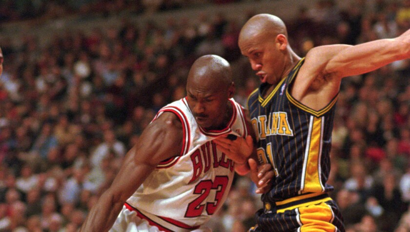 Bulls star Michael Jordan tries to keep control of the ball in front of Pacers standout Reggie Miller during a game in February 1998.