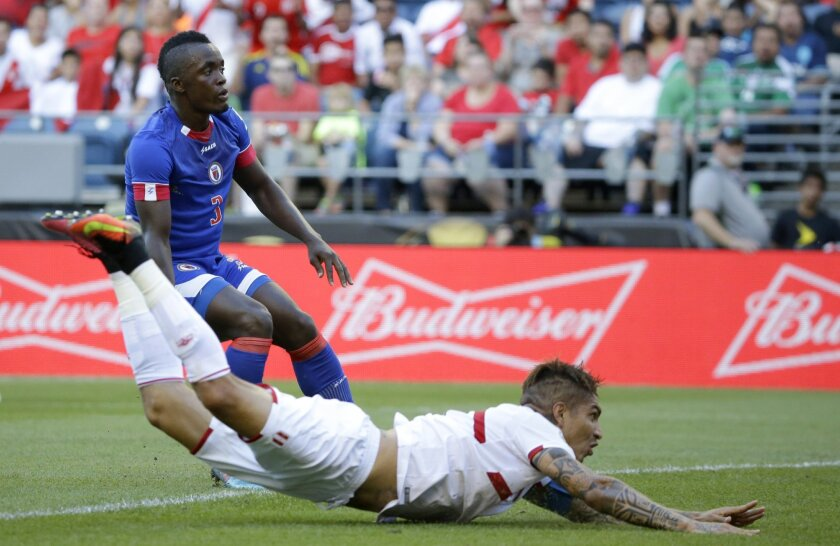 Peru forward Paolo Guerrero, right, hits the ground after he headed in a goal in the second half of a Copa America Centenario soccer match as Haiti defender Mechack Jerome looks on at left, Saturday, June 4, 2016, in Seattle. (AP Photo/Ted S. Warren)