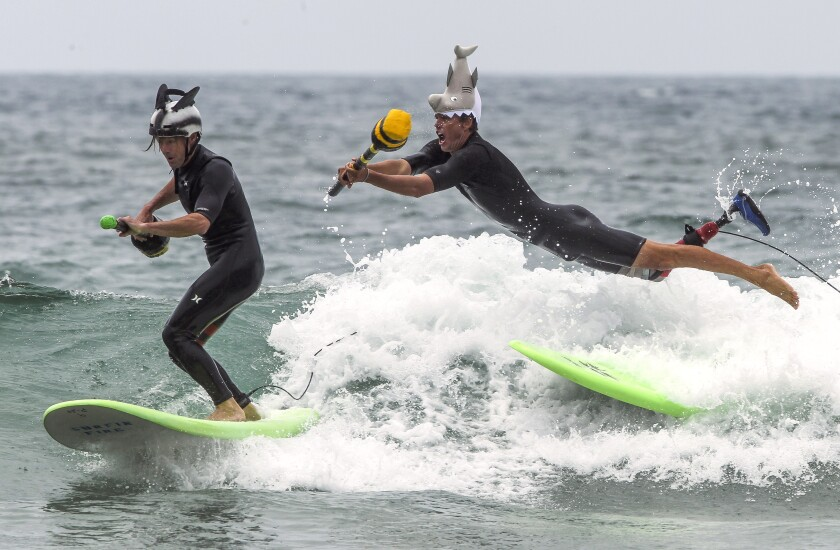 Mike Coots leaps from his surfboard in an attempt to knock Switchfoot band member Jon Foreman off his board as they compete in the surf joust during the Switchfoot Bro-Am music and surf festival at Moonlight Beach on Saturday in Encinitas.