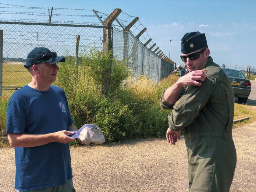 This photo made available by RAF Lakenheath on Friday July 23, 2021, shows U.S. Air Force Maj. Grant Thompson ripping the flight patch from his shoulder to give to Ian Simpson, left, as they meet at the viewing area outside RAF Lakenheath on July 20, 2021. Photographer Ian Simpson was honored by the 48th Fighter Wing for alerting Lakenheath about the troubles when he realized the pilot wasn't aware of the issue. (Capt Marie Ortiz/RAF Lakenheath via AP)