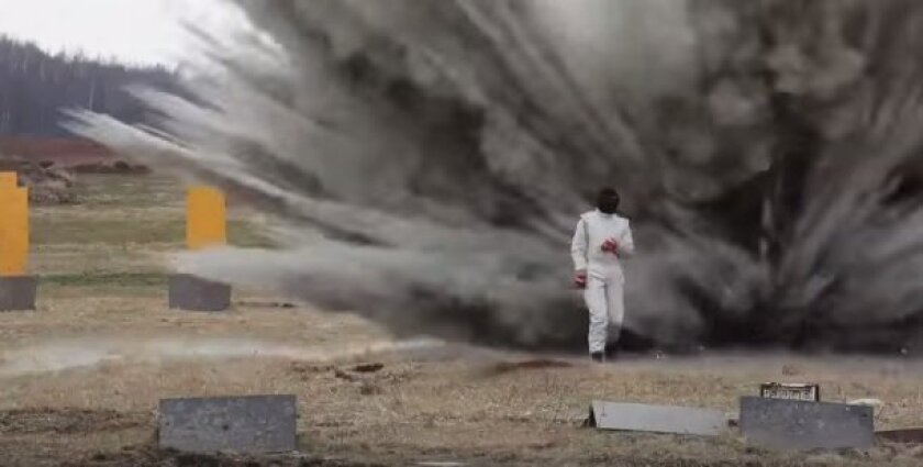 This screen grab from YouTube video shows a Russian woman walking through a minefield in an explosion-proof suit.