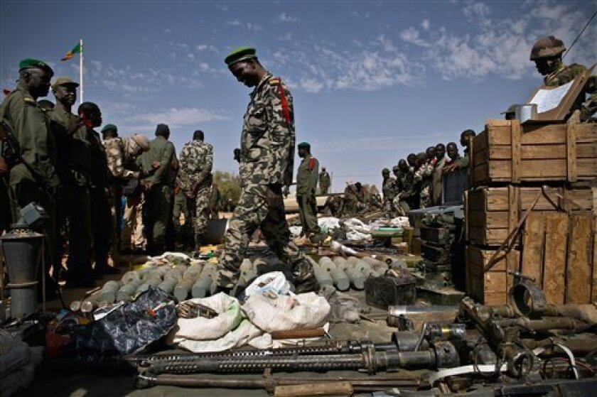 Malian soldiers look on as weapons, munitions, and other paraphernalia seized from radical Islamist rebels are displayed at the French army base in Gao, Mali, Sunday, Feb. 24, 2013. The Chadian army said Saturday that its troops had killed 65 Islamic extremist rebels and destroyed five vehicles in