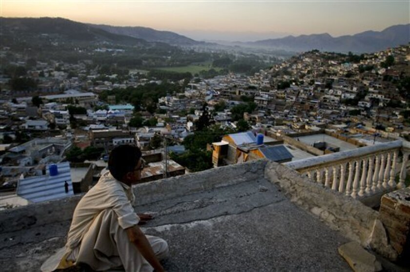 FILE - In this May 15, 2011 file photo, Ali Raza sits on the rooftop of his house as he views the city of Abbottabad, Pakistan. Pakistani officials say the government plans to build a recreation complex in the town. Syed Aqil Shah, sports and tourism minister in Khyber Pakhtunkhwa province, said Monday, Feb. 4, 2013 that the project in Abbottabad will have a zoo, paragliding club and water sports facilities. It will also have cultural heritage park. (AP Photo/Anjum Naveed, File)