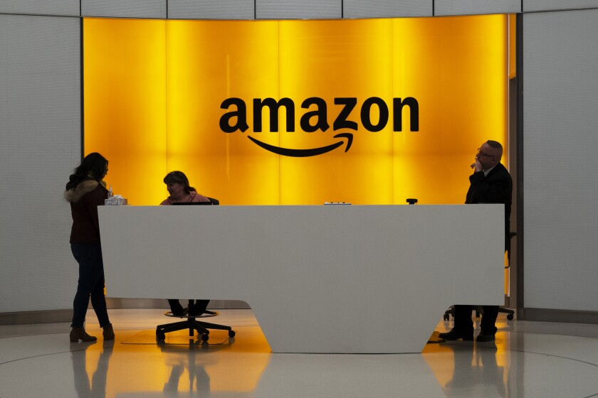 FILE - In this Feb. 14, 2019, file photo, people stand in the lobby for Amazon offices in New York. Amazon, which has been under pressure from shoppers, brands and lawmakers to crack down on counterfeits on its site, said Monday, May 10, 2021, that it blocked more than 10 billion suspected phony listings last year before any of their offerings could be sold. (AP Photo/Mark Lennihan, File)