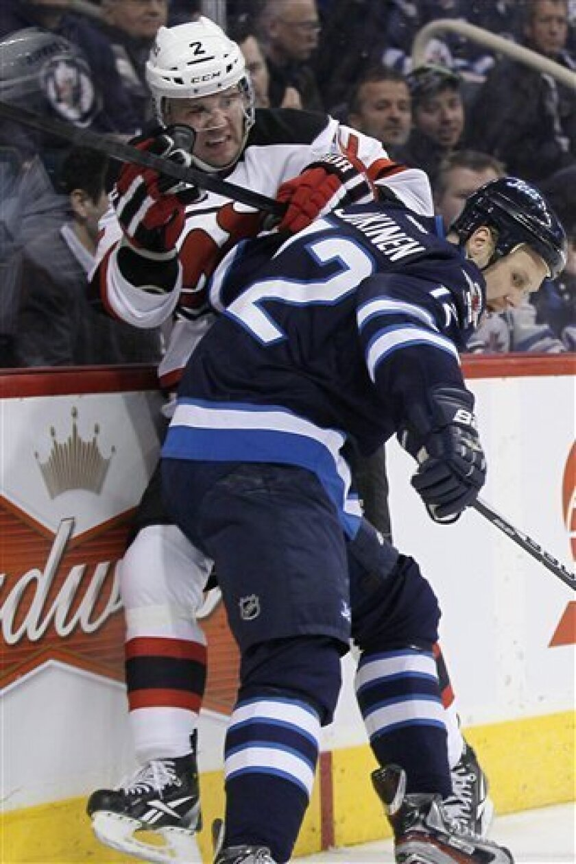 New Jersey Devils' Marek Zidlicky (2) is checked by Winnipeg Jets' Olli Jokinen (12) during the second period of an NHL hockey game in Winnipeg, Manitoba, on Thursday, Feb. 28, 2013. (AP Photo/The Canadian Press, John Woods)