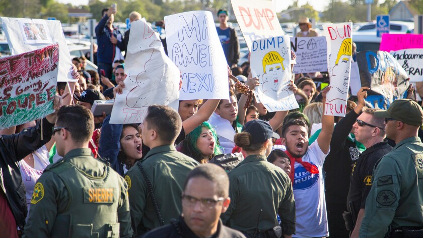 Orange County sheriff's deputies separate protesters from Donald Trump supporters during a rally in Costa Mesa.