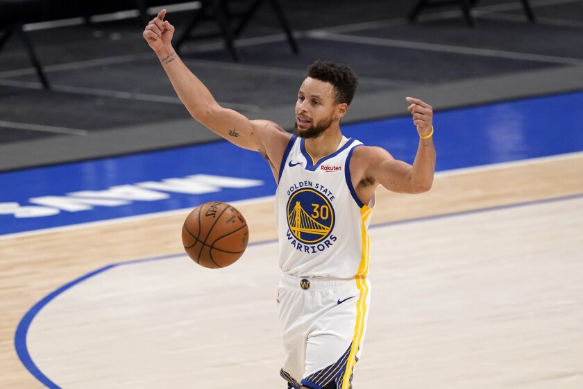 Golden State Warriors' Stephen Curry instructs teammates during an offensive possession in the second half of an NBA basketball game against the Dallas Mavericks in Dallas, Saturday, Feb. 6, 2021. (AP Photo/Tony Gutierrez)