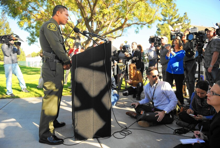 Phuong Nguyen, an Orange County Sheriff's deputy, speaks to the media in Vietnamese at a news conference in Santa Ana.