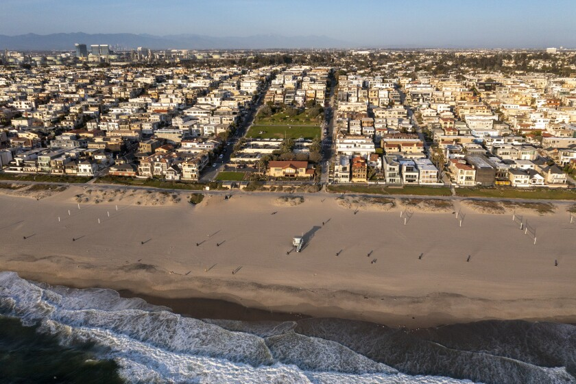 Manhattan Beach, CA - March 24: An aerial view of Bruce's Beach at sunset. Los Angeles County is trying to give the land back to the Bruce family, a Black family that was pushed off Bruce's Beach a century ago by Manhattan Beach. Bruce's Beach was one of the most prominent Black-owned resorts by the sea.The Bruce family used to have a resort right on the strand where the Los Angeles County Lifeguard Division office is and was popular with Black beachgoers. The Bruce's Beach plaque is at the top of the hill, but the actual Bruce property is the lifeguard building at the bottom of the hill, on the Strand at Bruce's Beach between 26th Street and 27th Street on Wednesday, March 24, 2021 in Manhattan Beach, CA. (Allen J. Schaben / Los Angeles Times)