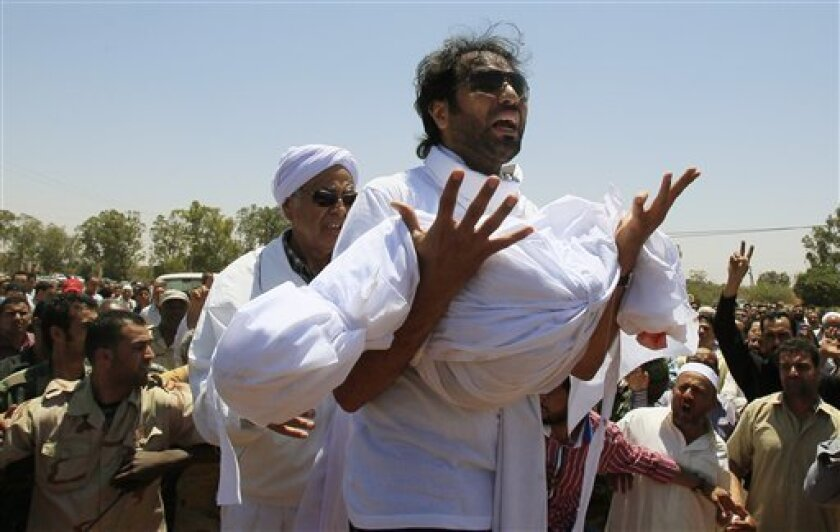 In this photo taken during a government-organized tour, Khaled, center, son of Khoweildi al-Hamidi, a close associate of Moammar Gadhafi, left, shouts while holding the body of one of his children, during a funeral in the city of Surman, some 60 km (40 miles) west of Tripoli, Libya, Wednesday, June 22, 2011. Libya's government said a NATO airstrike early Monday on a large family compound belonging to Khoweildi al-Hamidi killed at least 15 people, including three children. (AP Photo/Ivan Sekretarev)
