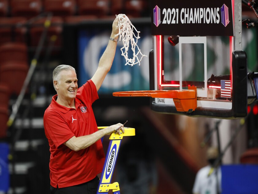 SDSU coach Brian Dutcher holds the net after beating Utah State to win the Mountain West tournament.