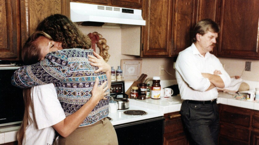 Lisa ByBee, stepsister of victim Michael Baker, hugs friend Valerie Giefer after learning of the las