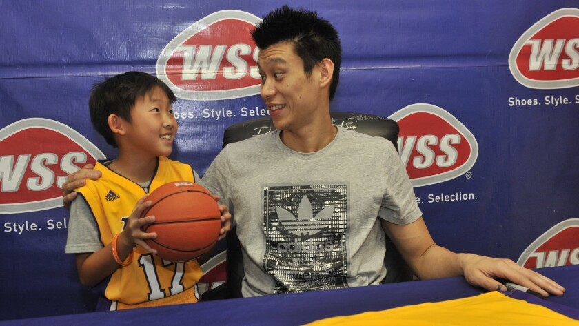 Lakers guard Jeremy Lin meets with a young fan while signing autographs in Lincoln Heights on Saturday.