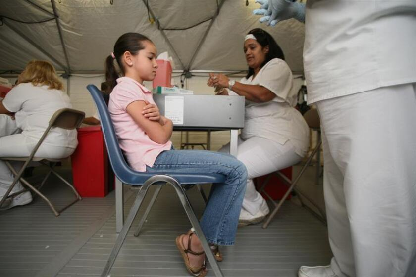 Una niña se prepara para que le pongan una vacuna contra la gripe AH1N1 en un hospital de San Juan, Puerto Rico. EFE/Archivo