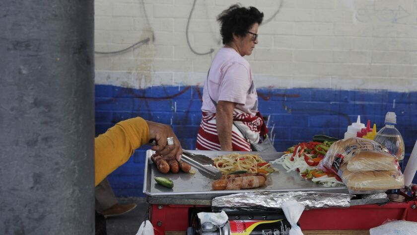 A food vendor prepares hot dogs on a sidewalk Tuesday, Nov. 27, 2018, in Los Angeles. They seem to b
