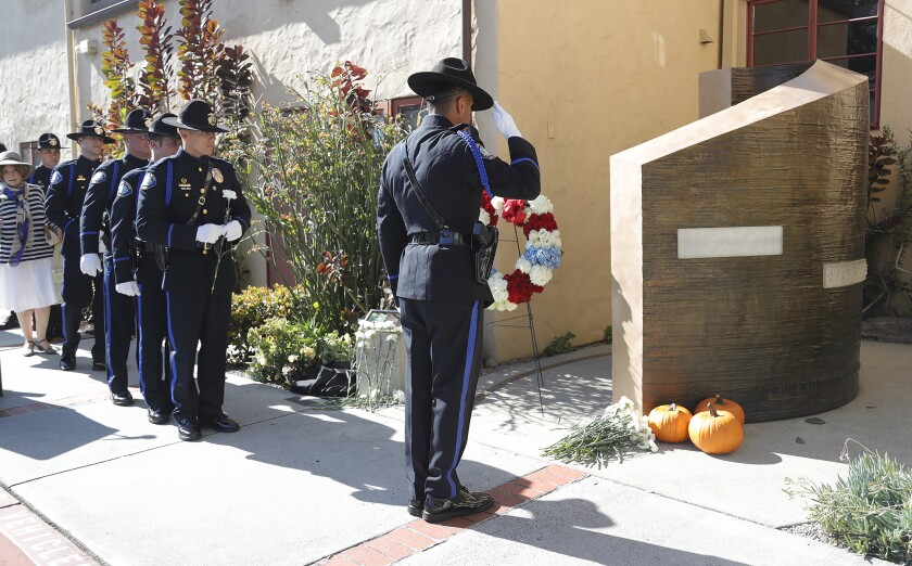 Laguna Beach Police Department officers and color guard salute the fallen officers memorial during the remembrance ceremony.