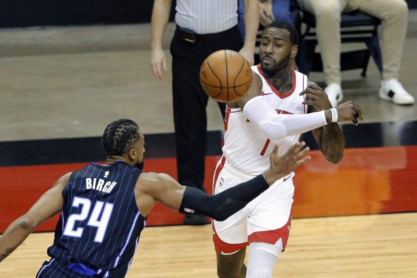 Houston Rockets guard John Wall, right, passes the ball past Orlando Magic center Khem Birch (24) during the first half of an NBA basketball game Friday, Jan. 8, 2021, in Houston. (AP Photo/Michael Wyke)