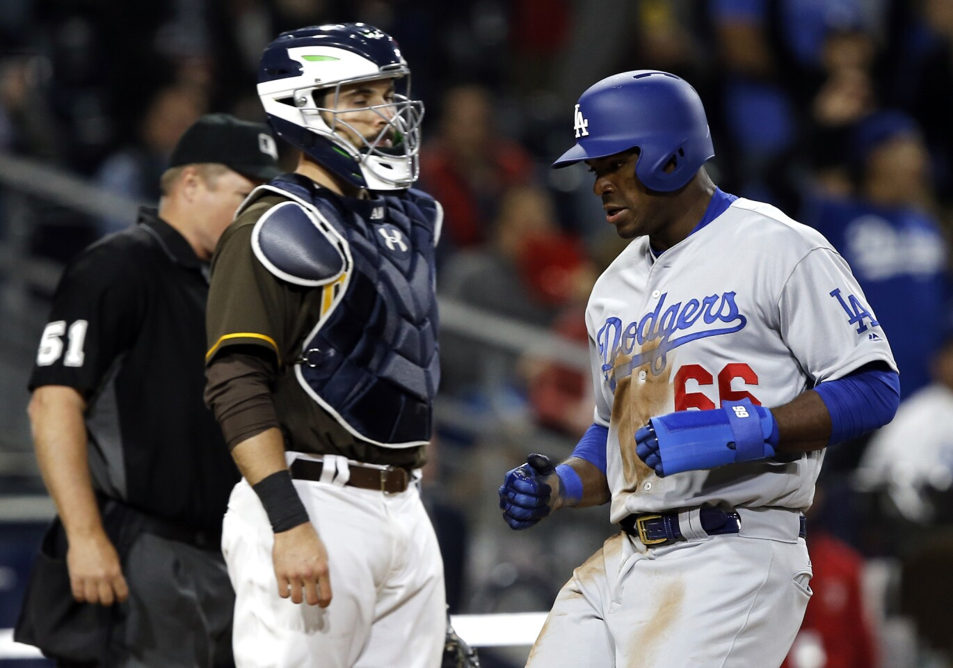 Los Angeles Dodgers' Yasiel Puig, right, scores in front of San Diego Padres catcher Austin Hedges on an infield single by Chris Taylor during the eighth inning of a baseball game in San Diego, Friday, May 5, 2017. (AP Photo/Alex Gallardo)