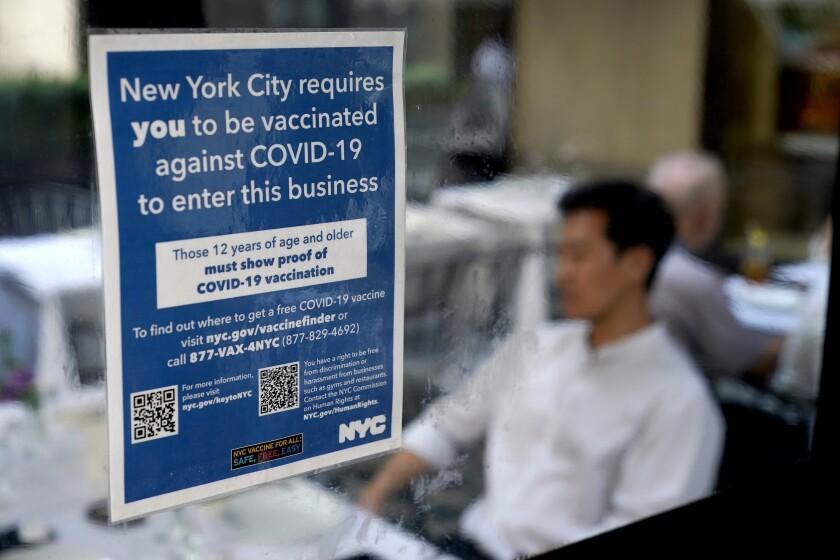 Aviso colocado en un restaurante que solicita a los comensales estar vacunados contra el COVID-19