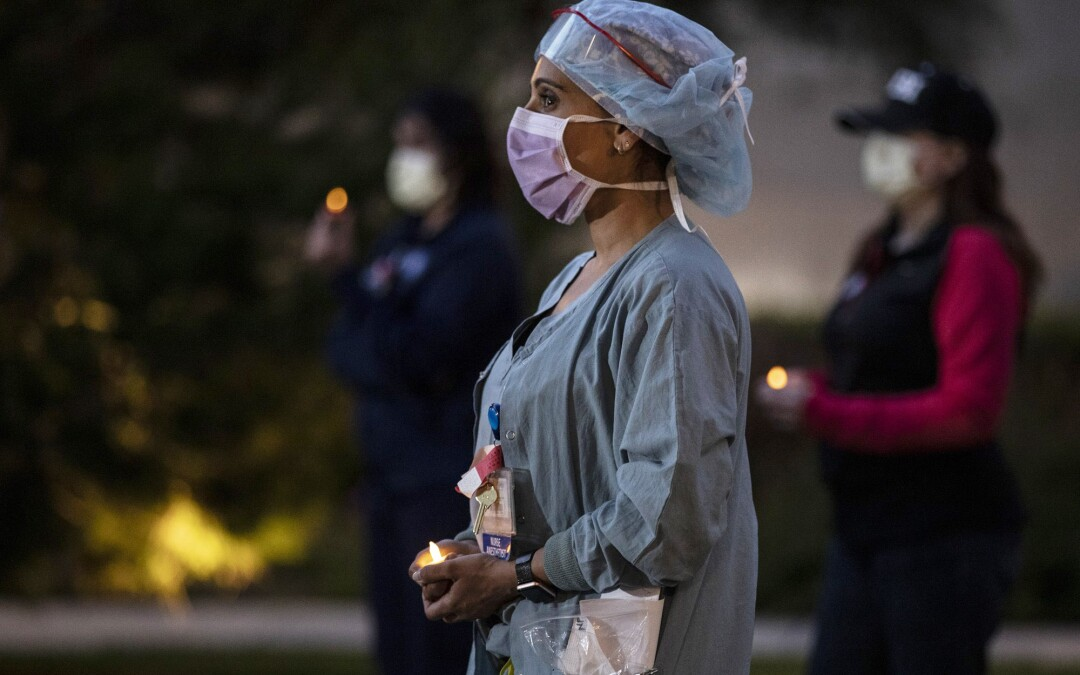 Nurse anesthetist Nilu Patel quietly stands with fellow nurses at UC Irvine Medical Center for an hourlong candlelight vigil at their shift change.