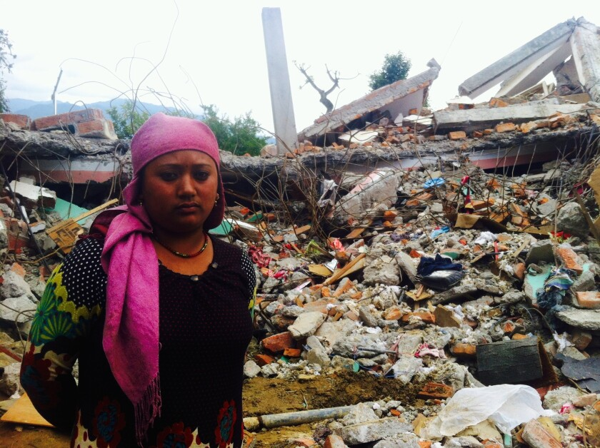 Prabina Shrastha stands in front of the wreckage of her home in Sangachok, Nepal.