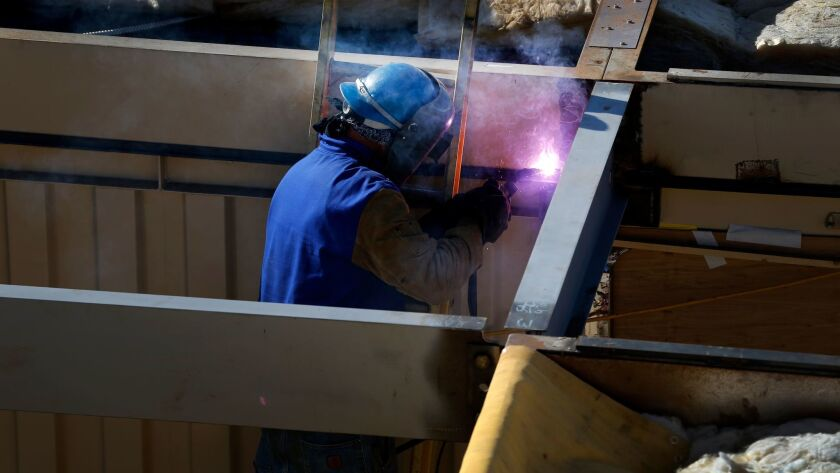 A worker welds together one of the two-story high pre-constructed shipping containers. Construction added the most jobs in the state last month.