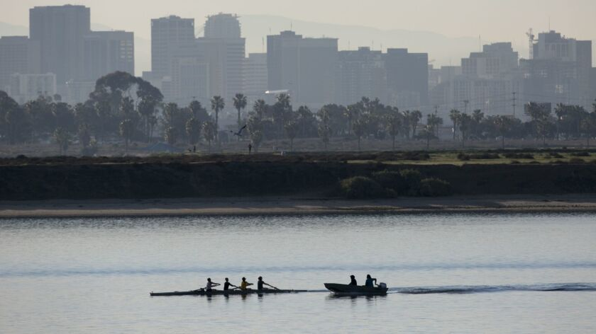 Rowers get in an early workout on Tuesday morning against the San Diego skyline before the waters get crowded later this week as teams from around the country arrive for the San Diego Crew Classic.