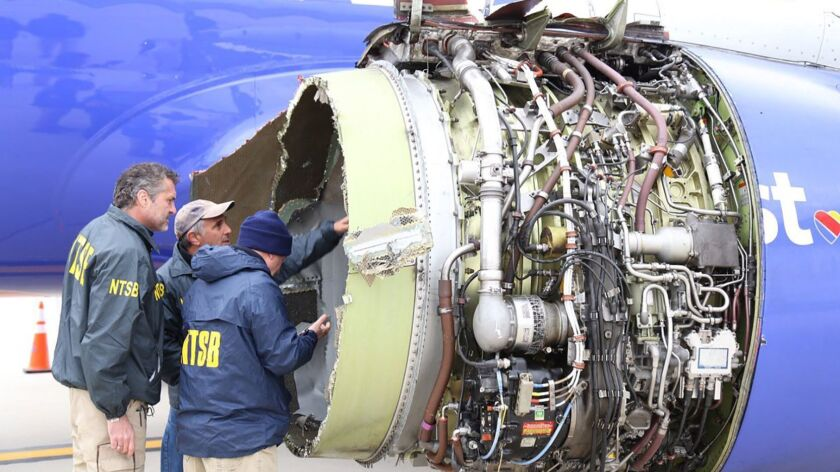 National Transportation Safety Board investigators in Philadelphia examine damage to the engine of the Southwest Airlines plane that made an emergency landing.