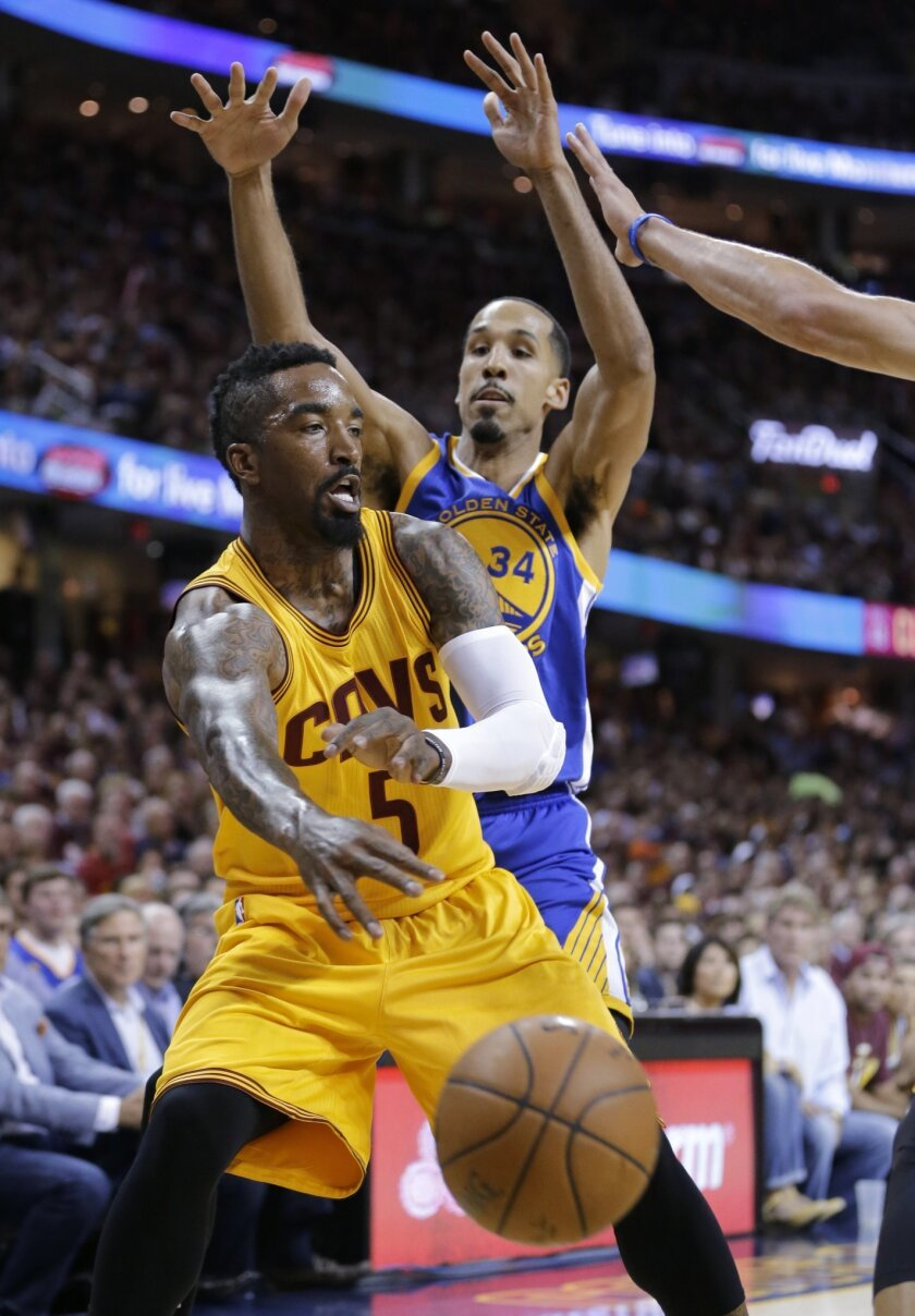 FILE - In this June 9, 2015, file photo, Cleveland Cavaliers guard J.R. Smith (5) makes a pass under pressure from Golden State Warriors guard Shaun Livingston during the first half of Game 3 of basketball's NBA Finals in Cleveland. A person familiar with the decision says Smith has agreed to re-sign with the Cavaliers. Smith declined his $6.8 million player option following the season. He looked at other teams before deciding to return to Cleveland, said the person who spoke to the Associated Press on Thursday night on condition of anonymity because the contract has not yet been signed. (AP Photo/Tony Dejak, File)