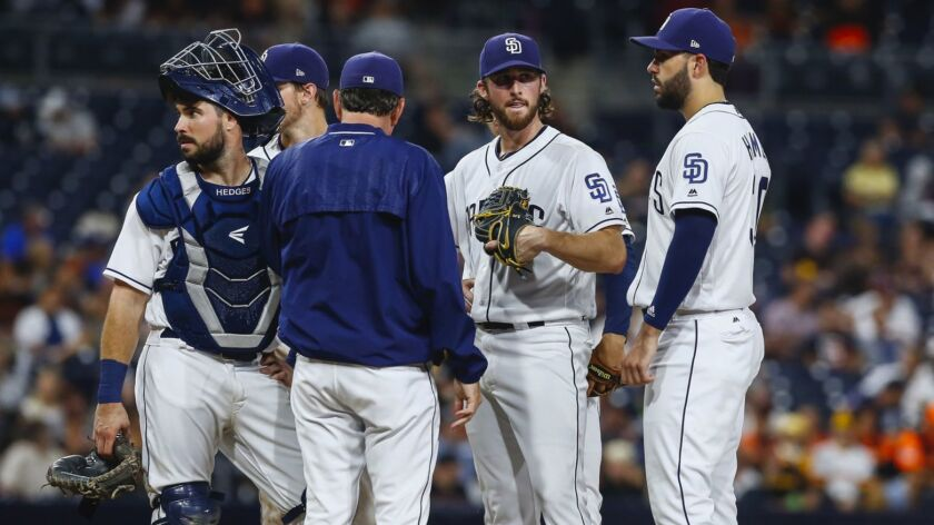 San Diego Padres starting pitcher Bryan Mitchell gets a mound visit from pitching coach Darren Balsley and the infield in the fifth inning.