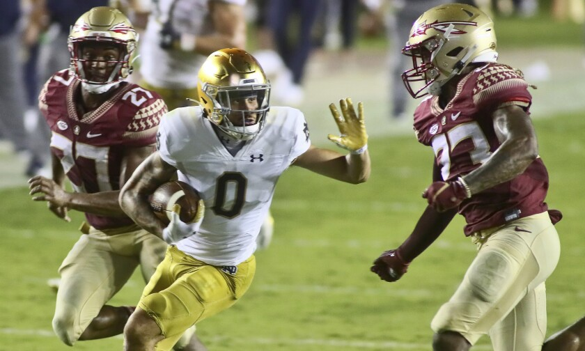 Notre Dame wide receiver Braden Lenzy tries to stiff arm Florida State defensive back Sidney Williams.