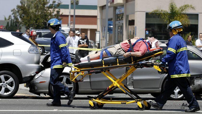 A crash victim is taken to an ambulance after a seven–car pileup near the intersection of Talbert an