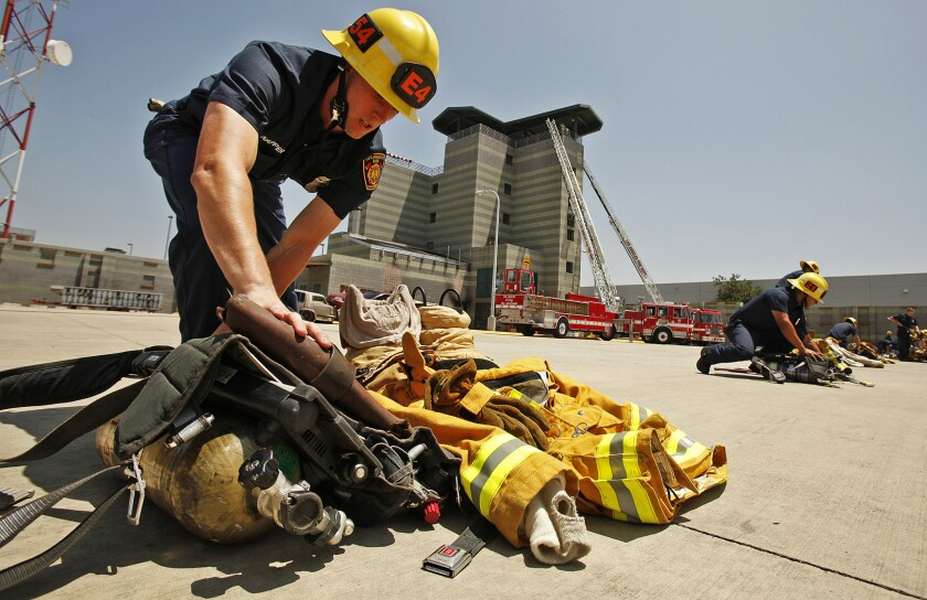 Christopher Napper, one of 70 recruits in the Los Angeles Fire Department class named in January, prepares his equipment for demonstrations during the recruit graduation ceremony in Panorama City.