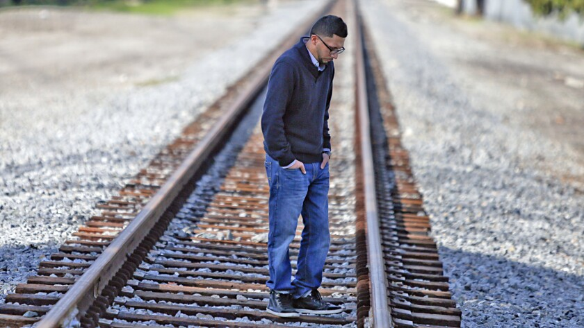 Kris Ramiriez stands on the railroad tracks in Paramount near where his brother, Oscar Ramirez, was killed by deputies in October.