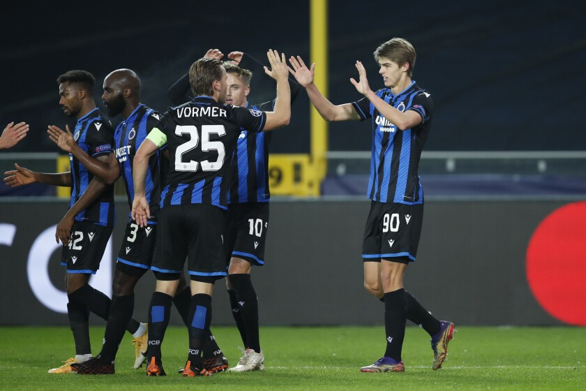 Brugge's Charles De Ketelaere, right, is congratulated after scoring the opening goal of the match during a Champions league Group F soccer match between Brugge and Zenit at the Jan Breydel stadium in Bruges, Belgium, Wednesday, Dec. 2, 2020. (AP Photo/Francisco Seco)