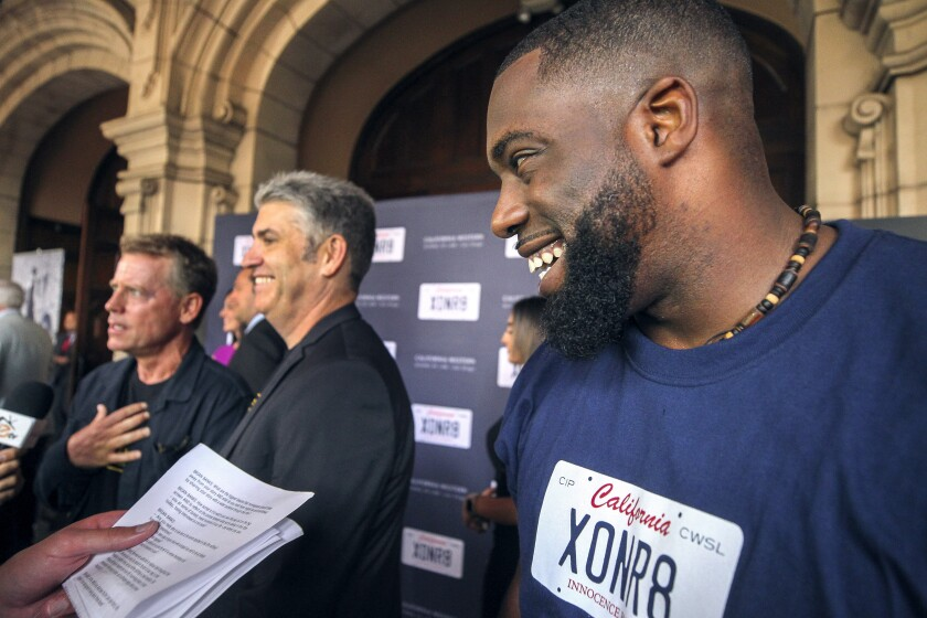 """Brian Banks, right, walks the red carpet next to Justin Brooks, center, of the California Innocence Project, and actor Greg Kinnear at a screening of the movie """"Brian Banks"""" at the Museum of Photographic Arts in Balboa Park on Saturday, August 3, 2019."""