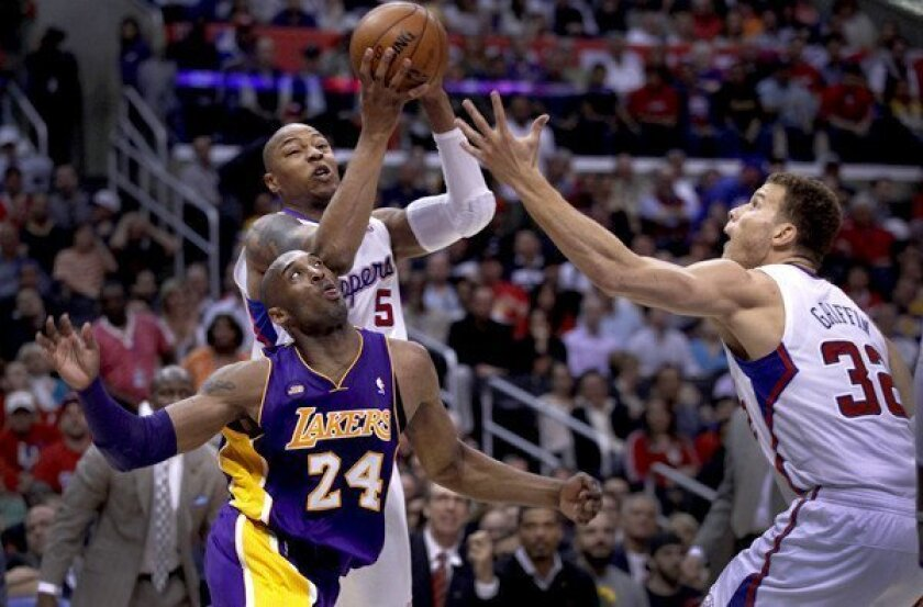 Clippers forward Caron Butler goes above Lakers guard Kobe Bryant to try to snag a rebound in the game Sunday afternoon.