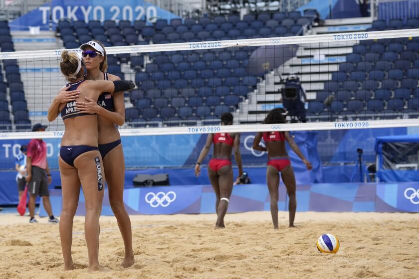 Las estadounidenses April Ross y Alix Klineman se abrazan durante un juego de voleibol de playa ante Cuba