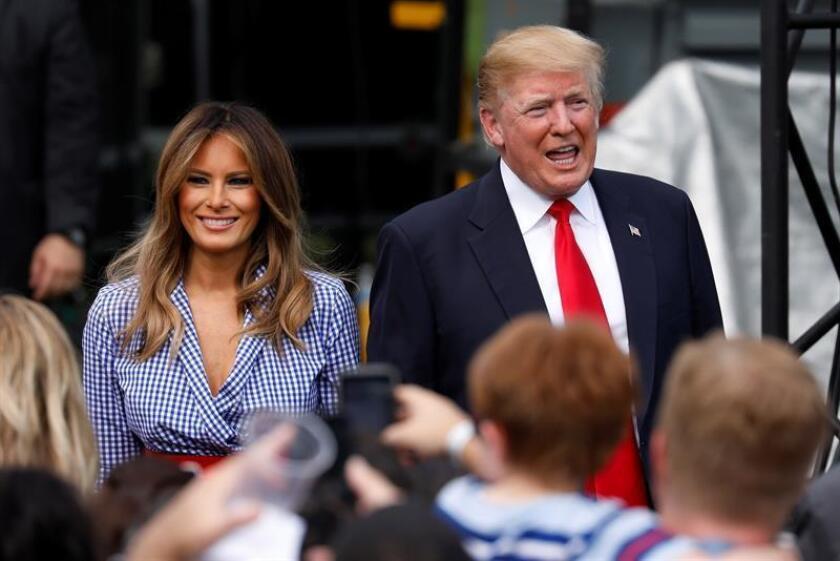 El presidente estadounidense, Donald J. Trump (d), y la primera dama, Melania Trump (i), saludan a invitados durante un picnic para familias de militares. EFE/POOL/Archivo