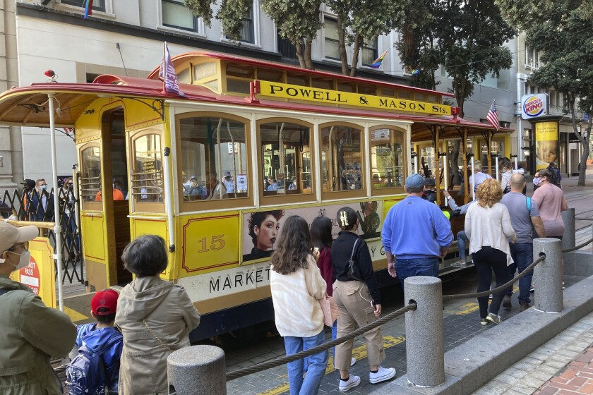 People line up to board a cable car in San Francisco