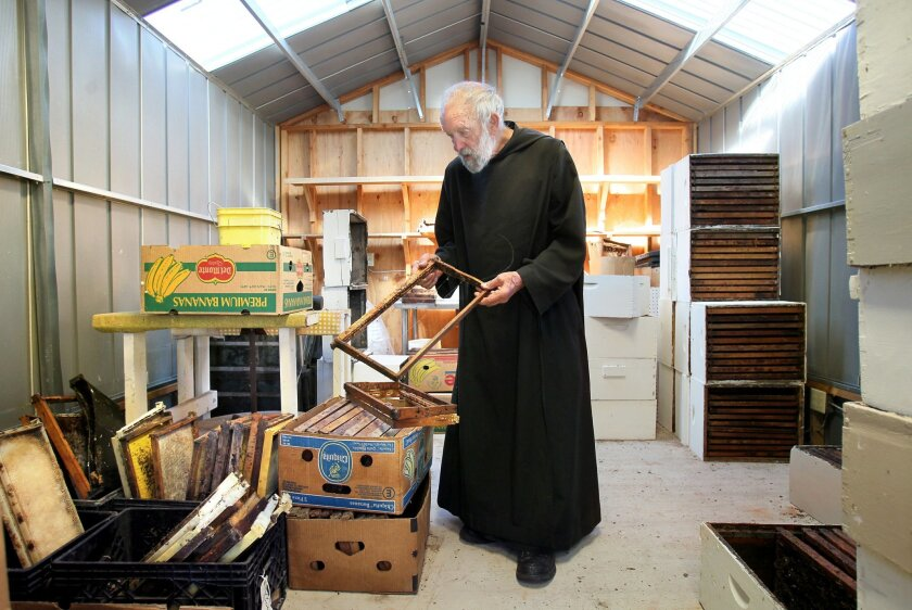 Brother Blaise Heuke, a Benedictine monk here at Oceanside's Prince of Peace Abbey, inspects a beehive frame to be repaired in his workshop there for his many beehives nearby. He's been taking care of his hives there for over 40 years.
