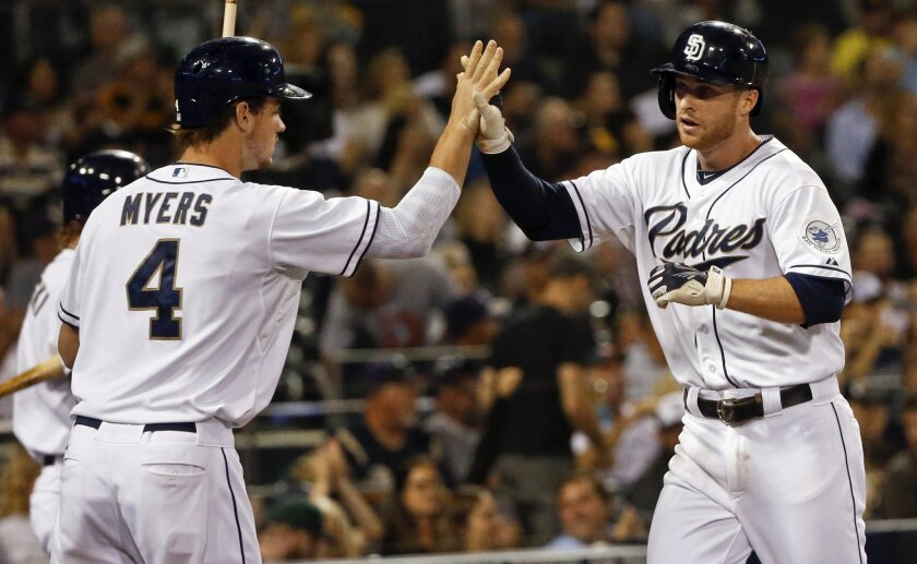 San Diego Padres' Cory Spangenberg high-fives with Wil Myers after scoring from third on a base hit by Padres' pitcher Tyson Ross in the fourth inning of a baseball game against the Milwaukee Brewers Tuesday, Sept. 29, 2015, in San Diego. (AP Photo/Lenny Ignelzi)