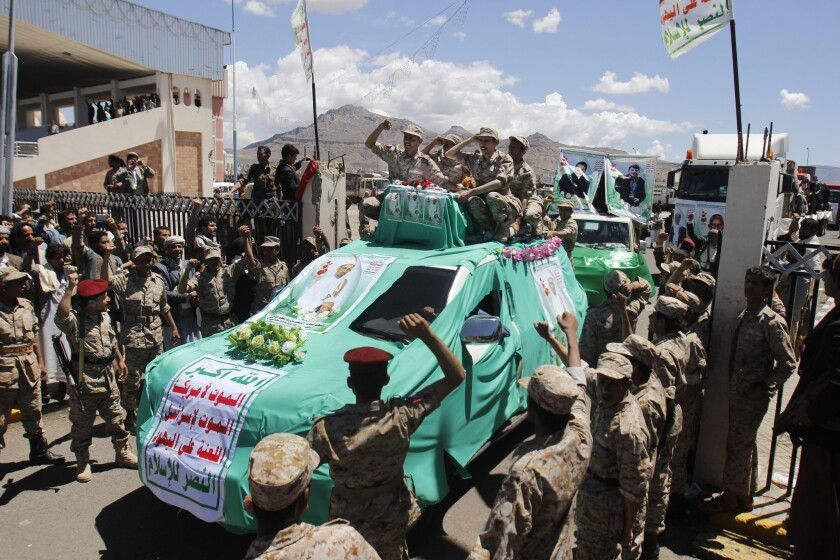 Houthi fighters chant slogans during the funeral procession for people killed last week in suicide bombings in Sana, Yemen.