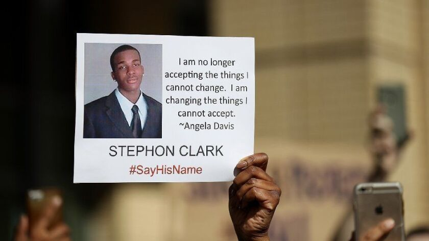 A protester holds a photo of Stephon Clark during a Black Lives Matter demonstration in Sacramento on March 22, 2018.