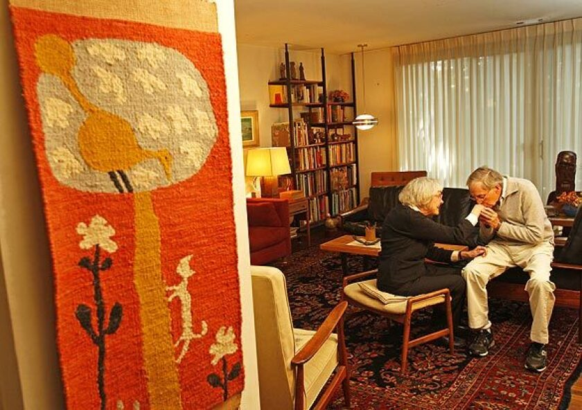 """Though little known to most of the public, Evelyn and Jerome Ackerman are revered in design circles for ceramics, tile mosaics, woodcarvings and textiles that had the kind of cheap-chic ethos so popular today. """"One of our goals was to be affordable,"""" Evelyn Ackerman says. """"Not having a lot of money was the position we were in most of our young life, so it is what we strove to do for others."""" The Ackermans invited the Home section for a peek inside their home and studio. Here, with her """"Cat and Bird"""" tapestry hanging by the living room, Evelyn Ackerman gets a little love from husband Jerome."""