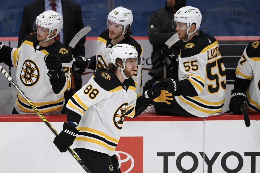 Boston Bruins right wing David Pastrnak (88) celebrates his goal with the bench during the second period of an NHL hockey game against the Washington Capitals, Monday, Feb. 1, 2021, in Washington. (AP Photo/Nick Wass)