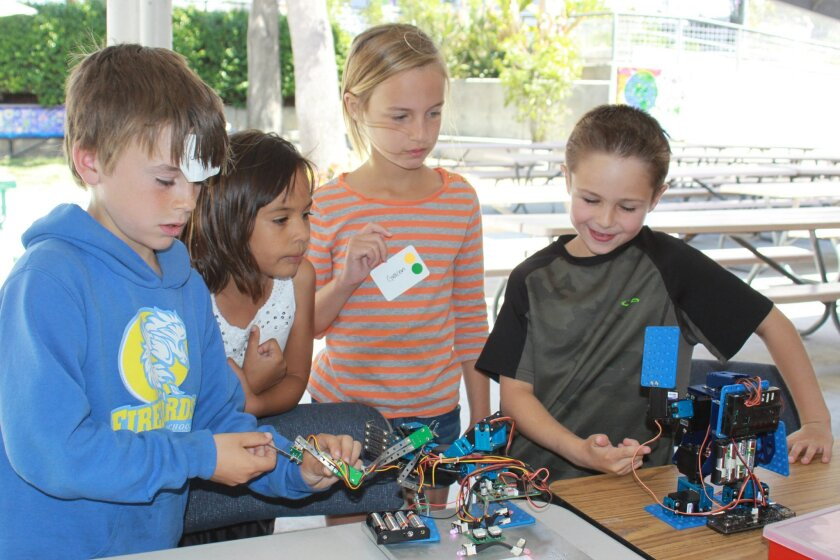 Jack Ryan, Irie Paris, Gracen Daniels and Cade Ballardo play with robots built by schoolmates.
