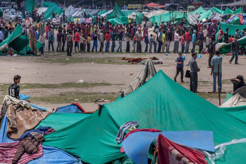 Residents line up for food in an evacuation area set up by the authorities in Tundhikel park in Katmandu, Nepal, on Monday.