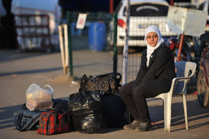 Syrian woman with her belongings at the Syrian-Turkish border near Hatay, Turkey.