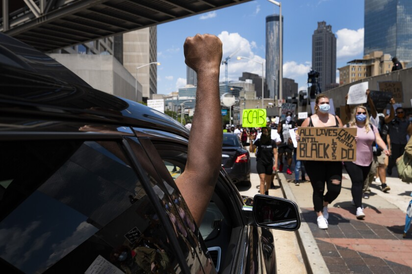 Passengers in cars show support for protesters marching in Atlanta on Saturday.